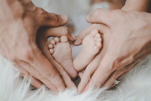 hands of parents holding the feet of a baby