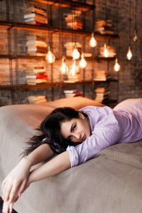 Attractive woman lying on bed, looks seductively at the camera