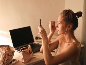 Woman applying makeup before a date night