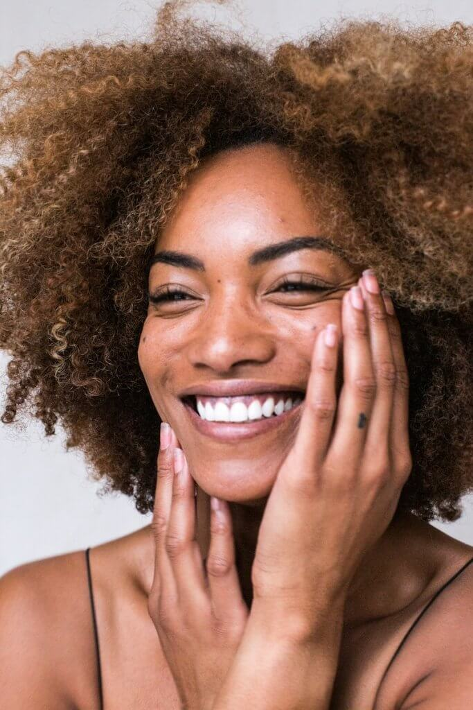 Woman of Color Smiling with Hands on Face