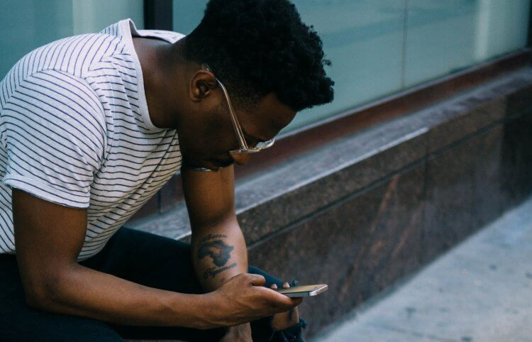 How to get over your ex blog post - Man hunched over looking at phone