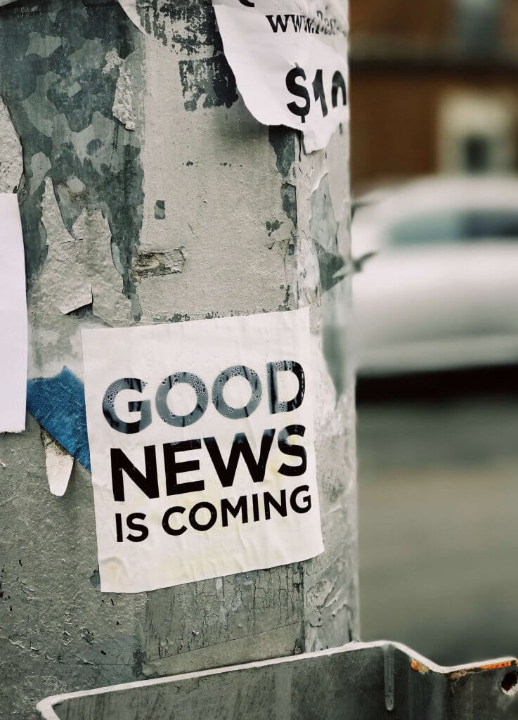 """Street pole with a piece of paper taped on it saying """"GOOD NEWS IS COMING"""""""