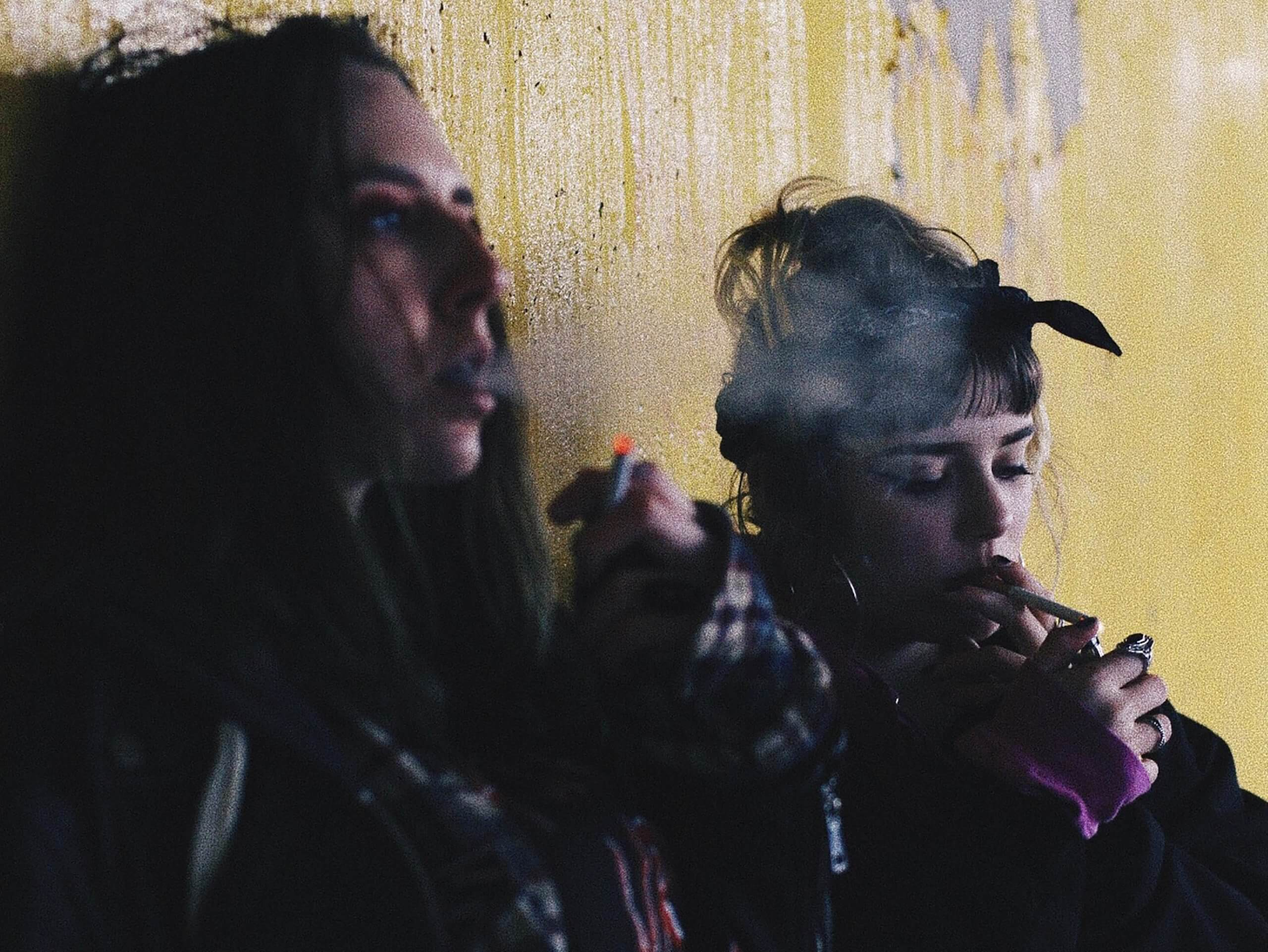 Two women doing drugs in an alley