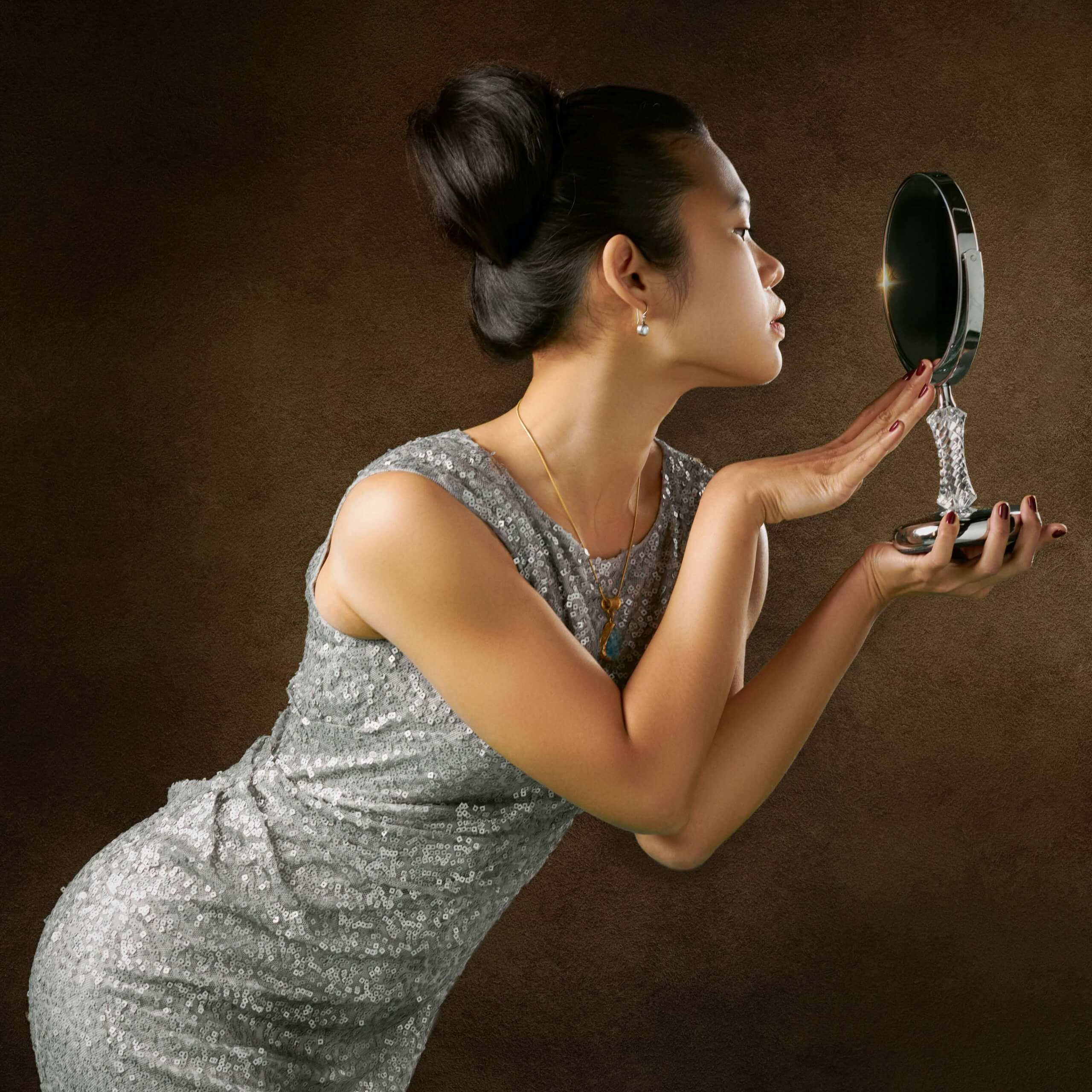 Maladaptive Schemas: Approval Seeking - beautiful woman in glitter ball gown looking in a mirror